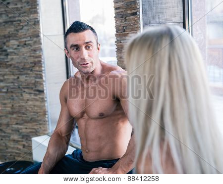 Muscular man and woman resting and talking at gym