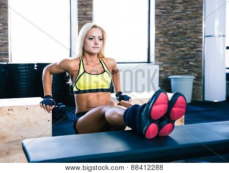 Beautiful sporty woman workout at gym on bench and fit box