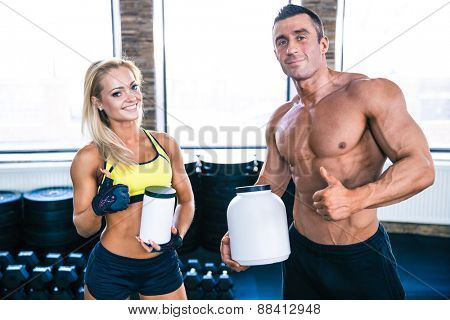 Man and woman holding container with sports nutrition and showing thumb up at gym