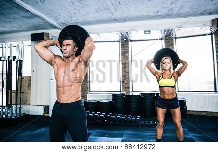 Muscular man and fit woman workout at crossfit gym