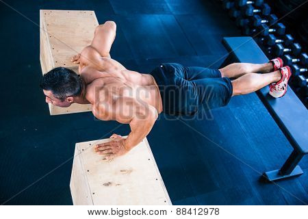 Muscular man doing push ups on fit box at gym