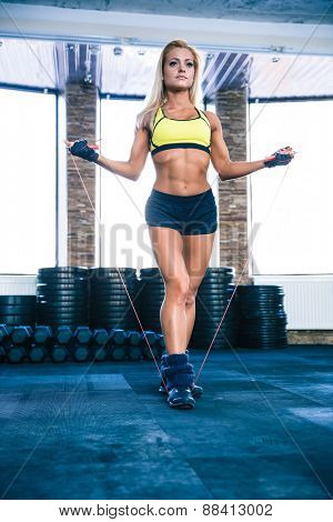 Young cute sporty woman workout with jumping rope in crossfit gym