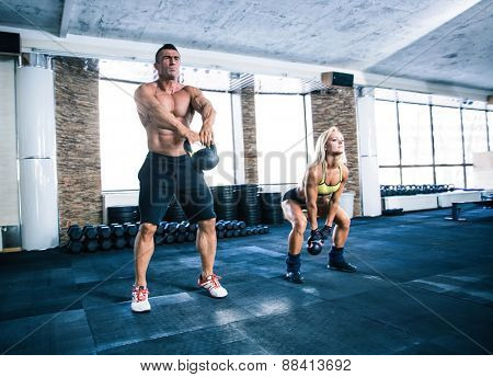 Group of a man and woman workout with kettle ball at gym