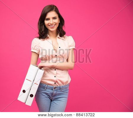 Smiling young woman holding folders over pink background and looking at camera