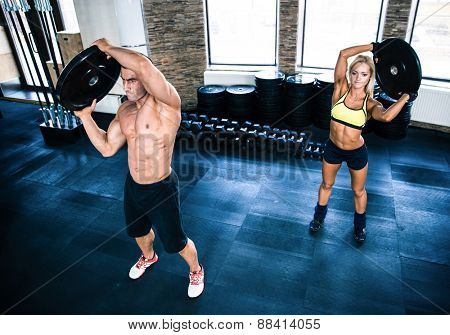 Muscular man and woman workout at crossfit gym