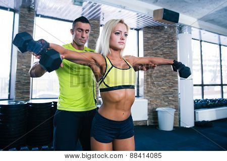 Fit woman lifting dumbbells with coach at gym