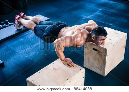Muscular man doing push ups on fit box and bench at gym