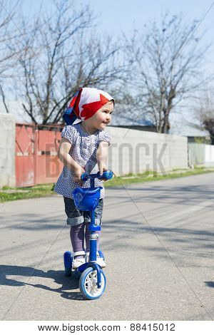Beautiful Baby Girl Rides Tricycle In Summer
