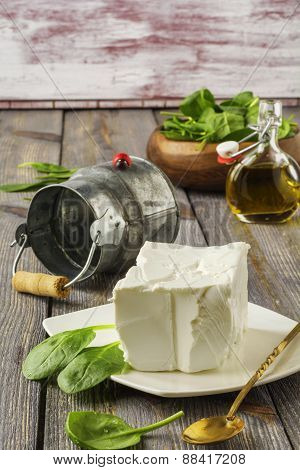 Feta cheese with olive oil and raw spinach .
