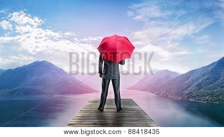 Man with umbrella standing on te pier
