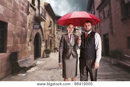 Business couple under umbrella