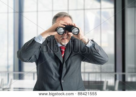 Businessman watching through binoculars