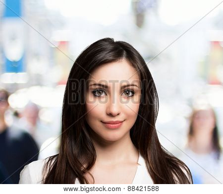 Beautiful young woman walking in a crowded urban street