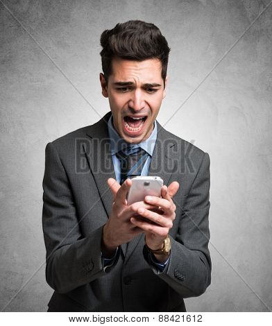 Portrait of a desperate man holding his mobile phone