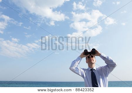 Businessman with binoculars looking upward against a sea and skyscape