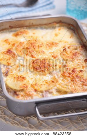 Potatoes a la dauphinoise in a baking dish. Selective focus on the potato crust