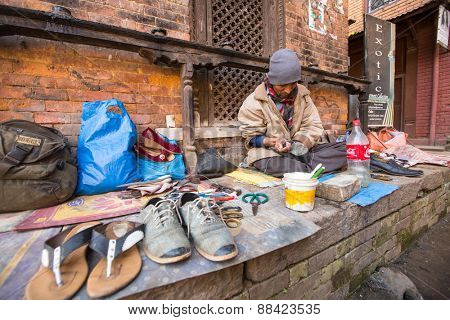 BHAKTAPUR, NEPAL - CIRCA DEC, 2013: Unidentified shoemaker works on the street. The caste system is still intact today but the rules are not as rigid as they were in the past.