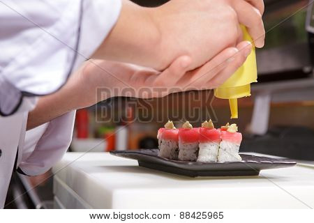 Sushi cook pours sauce