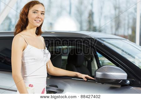Young pretty woman in car salon standing near car