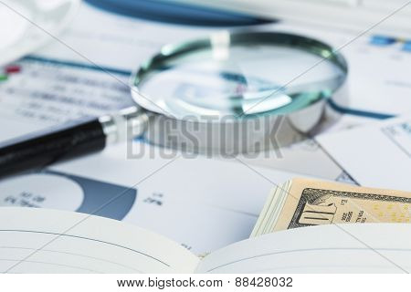 Magnifing glass and documents with analytics data lying on table
