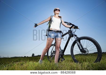 Low angle of young beautiful woman riding a bicycle in a park