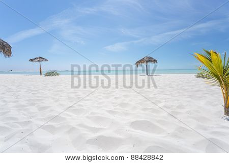 Exotic beach with white sand and umbrellas made of palm leafs
