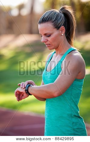 Image Of A Female Athlete Adjusting Her Heart Rate Monitor