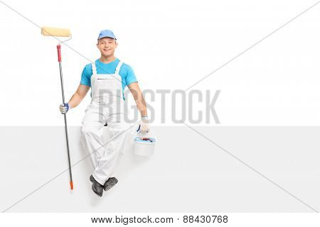 Young male painter sitting on a blank signboard and holding a paint roller and a color bucket isolated on white background
