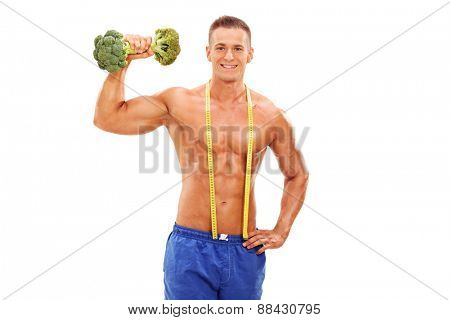 Handsome young athlete posing shirtless with a broccoli dumbbell in his hand and a measuring tape around his neck isolated on white background