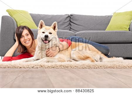 Young woman lying on the floor and hugging her pet dog next to a modern gray sofa isolated on white background