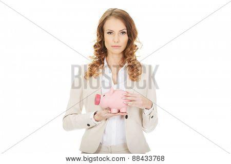 Business woman saving money in piggybank.