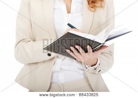 Businesswoman's hand writing in a note.