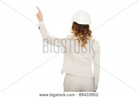 Architect businesswoman in white helmet pointing up.