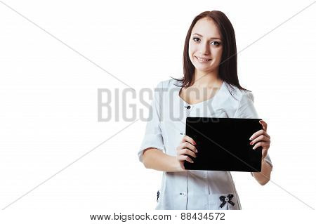 Young woman doctor in scrubs using a touchscreen computer