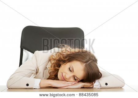 Tired businesswoman having a nap at her desk.