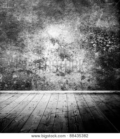 Vintage room interior with textured wall and wooden floor - black and white photo