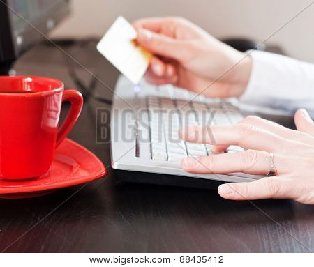 female hands holding a credit card over the desk in the office