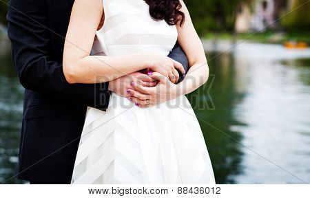 Newly wed couple embracing - focus on hands with wedding rings