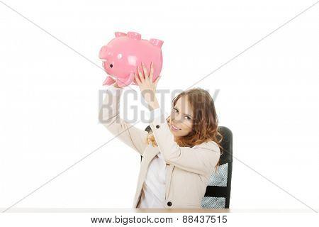 Business woman shaking a piggybank by a desk.