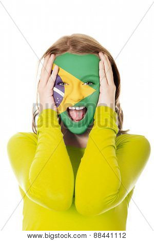 Woman with Brazilian flag painted on face.