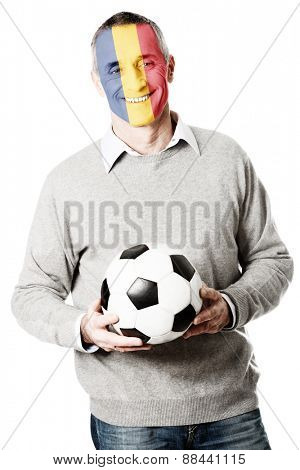 Mature man with Romania flag painted on face.