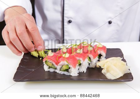 Cook adds wasabi and ginger to sushi rolls