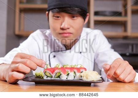 Cook puts seaweed on sushi