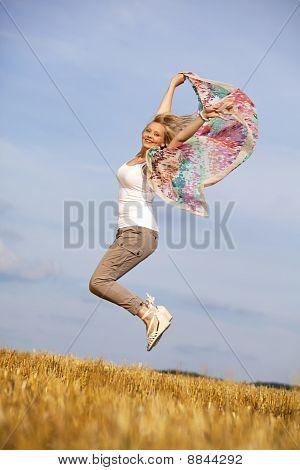 happy jumping blond teenage girl