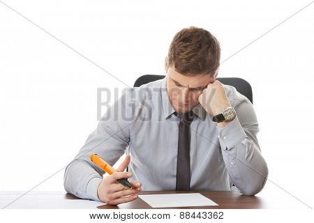 Worried businessman writing a note in the office.