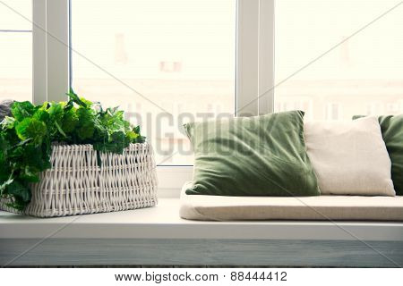 Pillows On The Windowsill And Plastic Window. Wicker Basket With Flowers On The Windowsill.