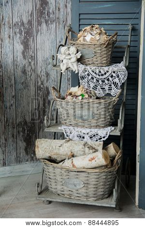 Background Rustic Veranda With A Shelf With Baskets And Angels