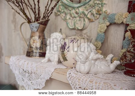Vintage Table With Two Angels, Clocks And Knitted Cloth