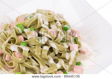 Pasta tagliatelle with green peas and ham.
