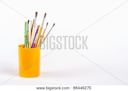 paints brushes in plastic beaker